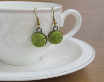 Antique bronze earrings and green fabric.