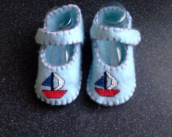 Baby boys blue felt booties with crosstitch sailboat.