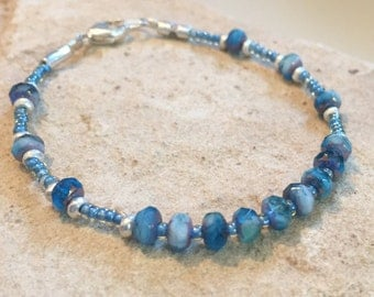 Blue bracelet made with Czech glass rondelle beads, Hill Tribe silver rondelle beads, seed beads, and silver tube beads with a trigger clasp