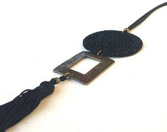 Collar con borla negro y colgante geométrico