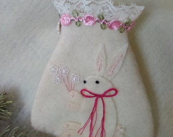A Christmas ornament that is one of a kind and handmade. I appliqued a rabbit on the front and she is carrying a bouquet of flowers.