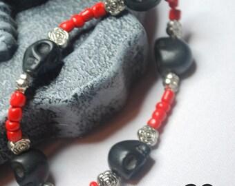 Skull bracelet, homemade jewellery with black howalite skulls and red beads.
