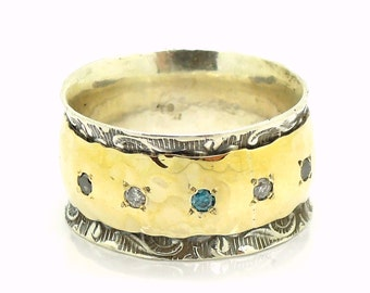 Diamond engagement ring set in a wide and curvy gold on silver band, mix color diamonds