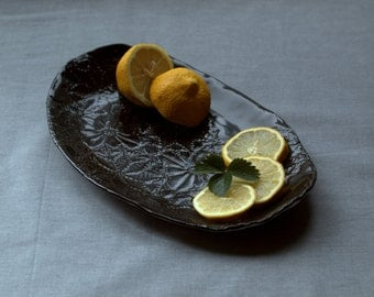Ceramic serving tray with impression of vintage textile.  Black porcelain tray.