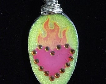 Red/yellow sacred heart spoon necklace.
