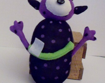 Sock Monster With Four Legs and One Eye With Four Spikes on Head and Big Smile with One Tooth Made from Purple and White Polka Dot Sock