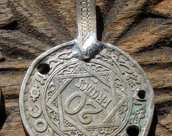 Tarnished Moroccan 20 franc coin with holes with brass bail or loop