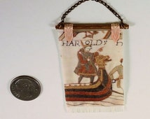Tapestry based on the Bayeux tapestry, bronze rod, white fringe, coral ribbon. Medieval or Tudor. 1 to 16 scale miniature. Hand made in USA.