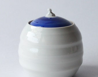 ceramic lidded container with tiny figure shaped knob