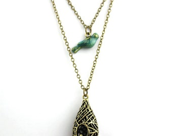 Antiqued layered necklace with enameled blue bird and pendant nest.