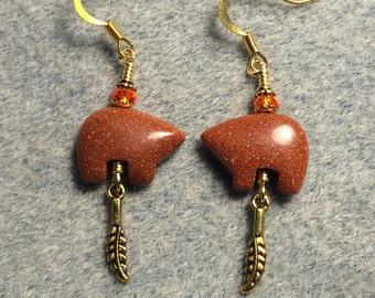 Orange goldstone gemstone Zuni bear fetish bead earrings adorned with tiny gold feather charms and orange crystal beads.
