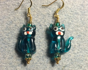 Translucent teal lampwork cat bead earrings adorned with teal Czech glass beads.
