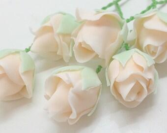 Small peachy pink sugar flower rosebuds.