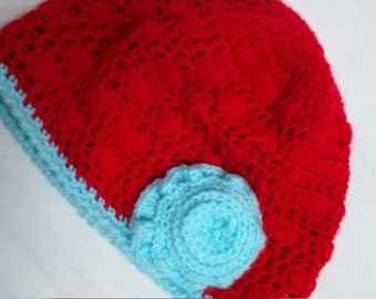Crochet hat to fit adult or child with flower decoration.