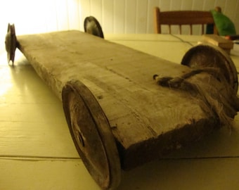 Vintage early farm toy or trolley. Made with barn wood and antique wheels.