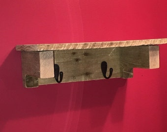 Salvaged pallet wood wall shelf with hooks.
