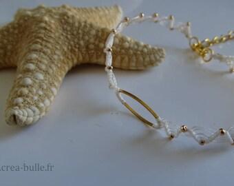 Bracelet woven in white macrame around a golden ring