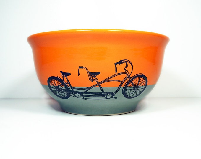 Featured listing image: large bowl shown glazed in a colour block of Creamsicle & Storm with tandem bicycle prints. Made to Order.