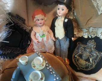 """Charming color print of vignette style scene with antique dolls, old fabrics, tiny teacups and other amazing old objects, 8"""" x 10"""", framable"""