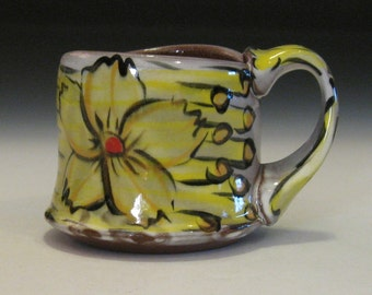 Yellow and orange flower mug with red dots and black stripes