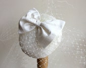 Ivory fascinator, silk bow, birdcage veil.