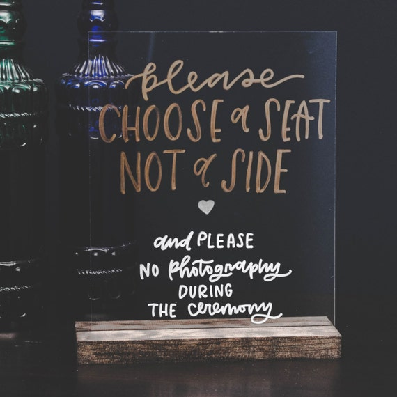 acrylic wedding sign saying choose a seat not a side and no photography please