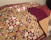 70 x 80 (queen size) quilt done in multiple red tone stars and 4 patches.  Pictures do not do it justice.  Machine quilted and hand bound.