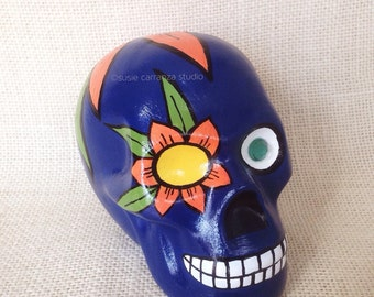 Hand painted ceramic skull by Susie Carranza. Navy blue with flower and gem eyes. Orange and yellow flowers.