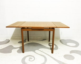 mid century modern dining table in teak  in very good original condition  with two draw leaves