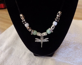 Dragonfly necklace on cloth cord, light green and black rhinestone beads, silver spacers. Easy hook closure. Necklace is 18 inches long.