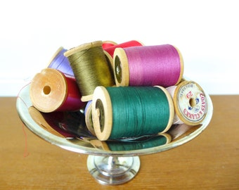 Fourteen large wooden spools with thread