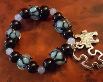 BRACELET: Beautiful Autism Awareness Blue and Black Lampwork Beaded Stretch Bracelet with Puzzle Charms