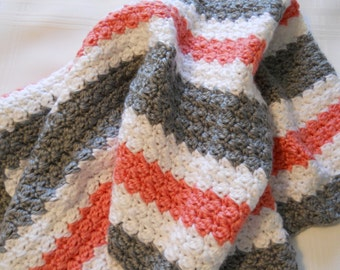 Baby blanket, crocheted in a soft white, grey and peach color.