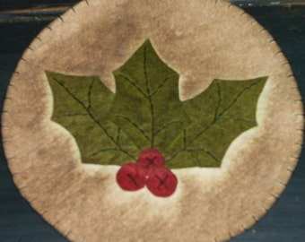 Candle mat holly measuring 8 inches across with a white background coffee dyed
