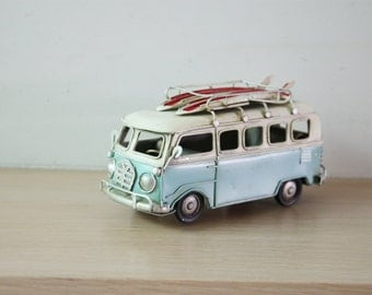 Blue and white VW van, vintage, retro collectible minty blue VW van miniature, with red surfboards on the bagage rack, mid nineties