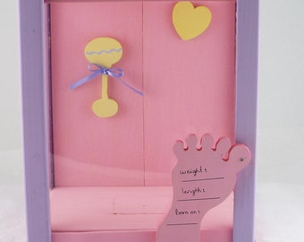 Pink Baby girl piggy bank with a foot that has a space for writing weight,length, and birthdate
