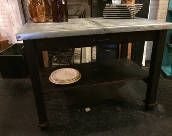 Kitchen island made from repurposed workbench with oxidized galvanized metal top