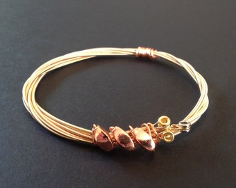 A handmade bronze acoustic recycled guitar string bracelet/bangle with 3 bronze beads