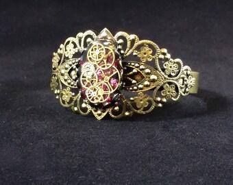 Steampunk Watch Gears Bracelet, watch gears and parts float above rose pink leaf glitter on an adjustable filigree bronze bracelet BR04