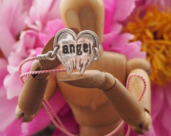 A handmade fine silver angel wings hand stamped with 'angel' on a pink silk bracelet...