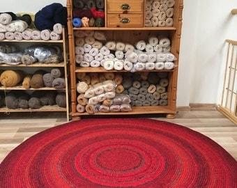 Handmade round rug in red, measures 59'' in diameter