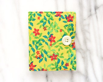 yellow floral needlebook with a white button closure with felt pages