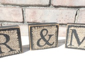 Wood Blocks Painted Black and Distressed with Black Block Lettering Painted Neatly on Burlap Squares