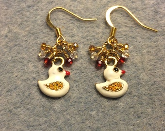 Off white enamel duck charm earrings adorned with tiny dangling red, amber and clear Chinese crystal beads.