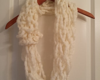 Arm knitted cream scarf.