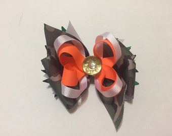 "Camo and bright orange 5"" stacked bow with remington 12 ga and rhinostone embellishment."