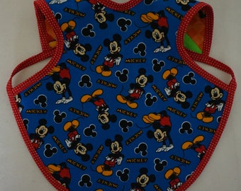 Mickey Mouse reversible Bapron (bib).  Flannel on one side and cotton on the other side.  Available in two sizes.