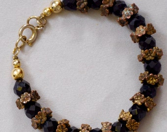 "7 1/4"" Vintage Jet black beads and gold toned flowers between, weight 13.3 gr."