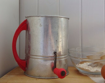 Vintage aluminium Kande Flour sifter with red handle