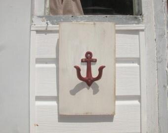 Nautical cast iron anchor hook, on pine